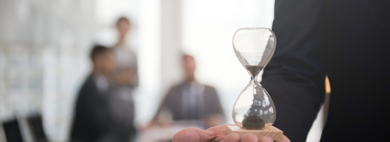 Businessman holding an hour glass, signifies the importance of being on time