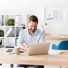 happy-bearded-man-sitting-in-office-working-4HVP863-150x150.jpg